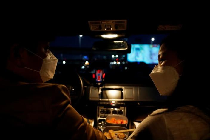 A couple prepares to watch a movie from their car at a drive-in theater that has been temporarily made for residents to enjoy movies while keeping social distancing following the outbreak of the coronavirus disease (COVID-19), in Seoul