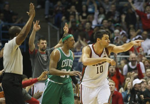 Milwaukee Bucks' Carlos Delfino (10) reacts to his three-point basket in front of Boston Celtics' Paul Pierce (34) during the first half of an NBA basketball game on Thursday, March 22, 2012, in Milwaukee. (AP Photo/Jeffrey Phelps)