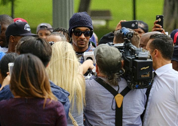 Rapper Snoop Dogg, center, is surrounded by media during a march in support of unification outside of the graduation ceremony for the latest class of Los Angeles Police recruits in Los Angeles, Friday, July 8, 2016, after the killings of multiple police officers in Dallas on Thursday night. (AP Photo/Richard Vogel)