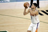 Phoenix Suns' Devin Booker shoots a go-ahead free throw during overtime of an NBA basketball game against the Milwaukee Bucks Monday, April 19, 2021, in Milwaukee. (AP Photo/Aaron Gash)