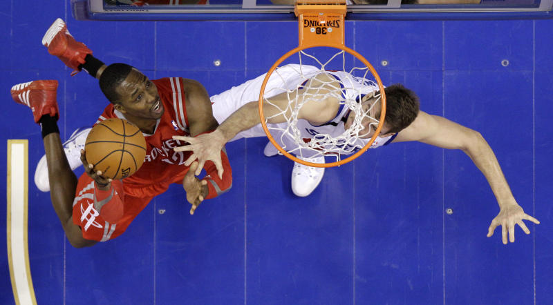 Houston Rockets' Dwight Howard, left, goes up for a shot as Philadelphia 76ers' Spencer Hawes defends during the first half of an NBA basketball game, Wednesday, Nov. 13, 2013, in Philadelphia. (AP Photo/Matt Slocum)