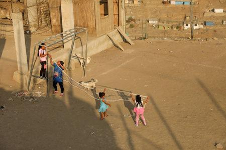 Women and children tie a volleyball net to a goal post before a volleyball match at a makeshift soccer field in Nueva Union shantytown in Villa Maria del Triunfo district of Lima, Peru, April 25, 2018. REUTERS/Mariana Bazo