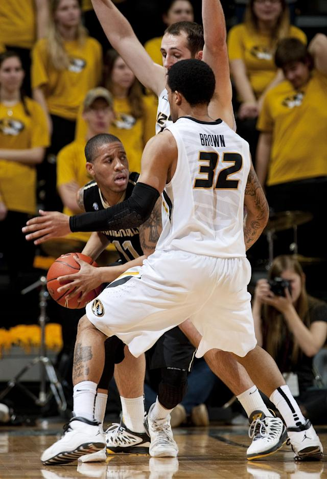 Vanderbilt's Kyle Fuller, left, looks to pass the ball around Missouri's Jabari Brown (32) and Ryan Rosburg during the first half of an NCAA college basketball game, Wednesday, Feb. 19, 2014, in Columbia, Mo. (AP Photo/L.G. Patterson)