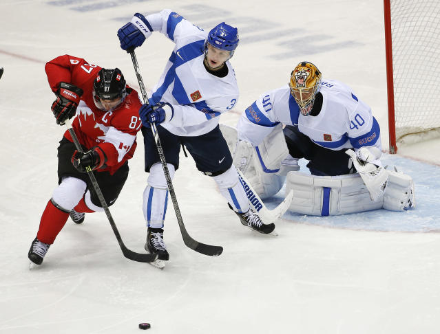 Canada forward Sidney Crosby battles for the puck against Finland defenseman Olli Maatta in the second period of a men's ice hockey game at the 2014 Winter Olympics, Sunday, Feb. 16, 2014, in Sochi, Russia. (AP Photo/Julio Cortez)