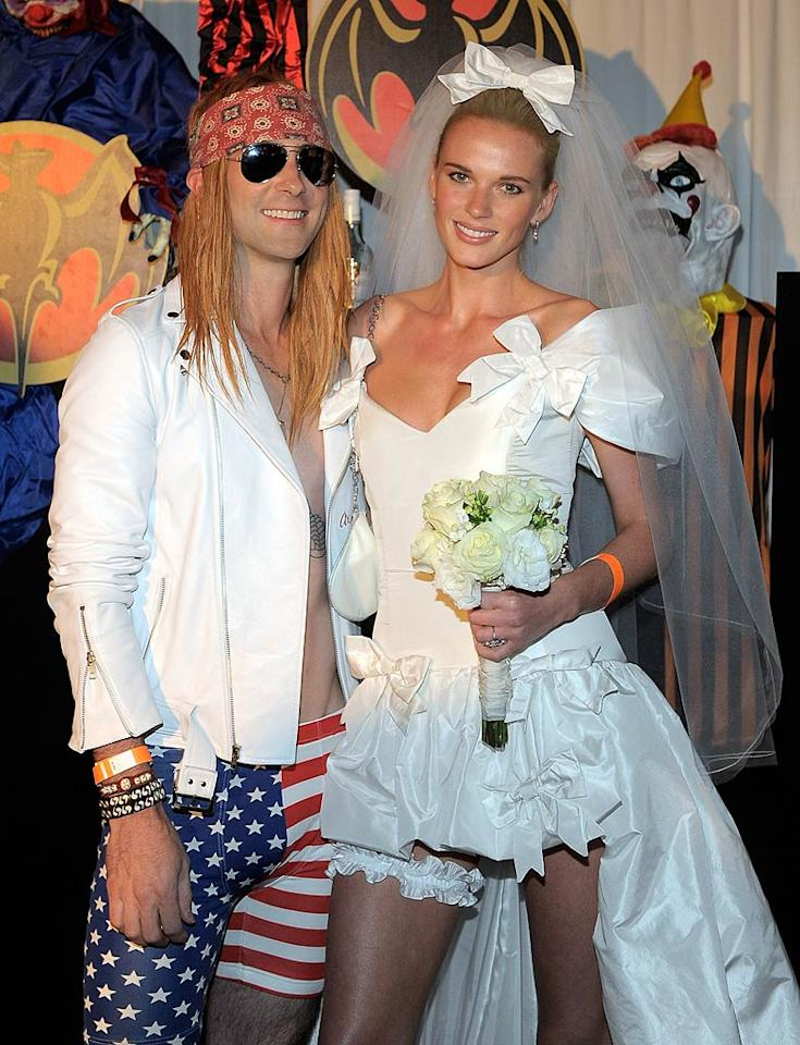 "One of the evening's hosts, Maroon 5 frontman Adam Levine, was barely recognizable in his Axl Rose costume. And in a nod to Guns N' Roses' ""November Rain"" video, Adam's girlfriend, model Anne V, posed as the bride that Axl's ex, Stephanie Seymour, played in the clip. (10/31/11)"