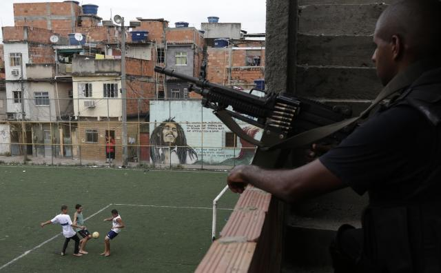 Boys play soccer as a policeman patrols one day after the occupation of the Mare slums complex in Rio de Janeiro
