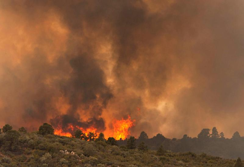 Flames top a ridge as the Yarnell Hill Fire moves towards Peeples Valley, Ariz. on Sunday, June 30, 2013. The fire started Friday and picked up momentum as the area experienced high temperatures, low humidity and windy conditions. It has forced the evacuation of residents in the Peeples Valley area and in the town of Yarnell. (AP Photo/The Arizona Republic, Tom Story)