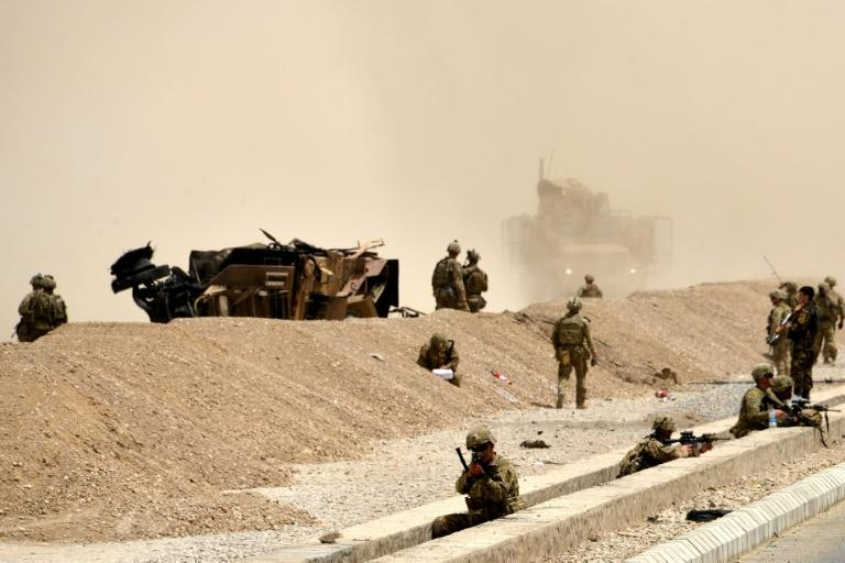 US soldiers keep watch near the wreckage of their vehicle at the site of a Taliban suicide attack earlier this month in Kandahar, Afghanistan