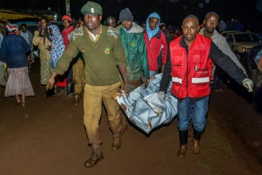 People carry a victim's body from a residential area on May 10, 2018 after the private Patel dam burst its bank at Solai, about 40 kilometres north of Nakuru, Kenya