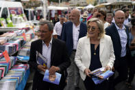 FILE - In this June 17, 2021, file photo, far-right leader Marine le Pen, right, and local candidate Thierry Mariani, left, campaign at an open air market of Six-Fours-les-Plages, southern France. Le Pen's once-ascendant far-right party is struggling ahead of runoff elections for France's regional leadership. Its best chance of victory is Mariani, a European lawmaker who meets regularly with Syrian dictator Bashar al-Assad and celebrated Russia's annexation of Crimea. (AP Photo/Daniel Cole, File)