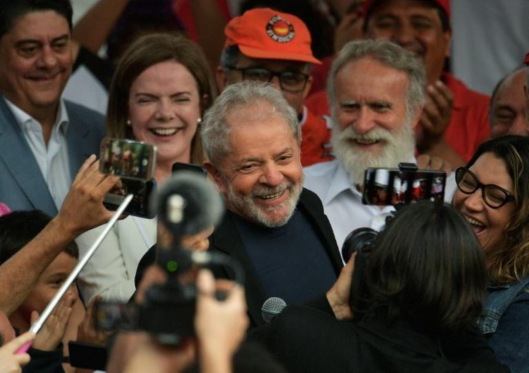 Former Brazilian president Luiz Inacio Lula da Silva smiles next to his girlfriend after leaving the federal police headquarters in Curitiba, where he was serving a sentence for corruption and money laundering