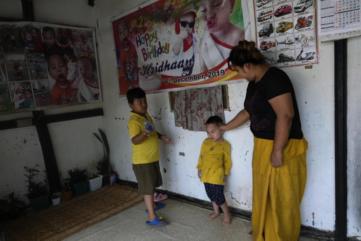 Diana Khumanthem, 30, plays with her three-year-old nephew Hridhaan, who she has decided to raise as her own after his mother Ranjita died of COVID-19, at home in Imphal, in the northeastern Indian state of Manipur, Monday, June 28, 2021. Diana lost both her mother and sister to the virus in May. Treatment costs wiped out the family's savings, and the private hospital where she died wouldn't release her sister's body for last rites until a bill of about $5,000 was paid. Data on global personal medical costs from the pandemic are hard to come by, but in India and many other countries treatment for COVID is a huge added burden at a time when hundreds of millions of jobs have vanished. (AP Photo/Yirmiyan Arthur)