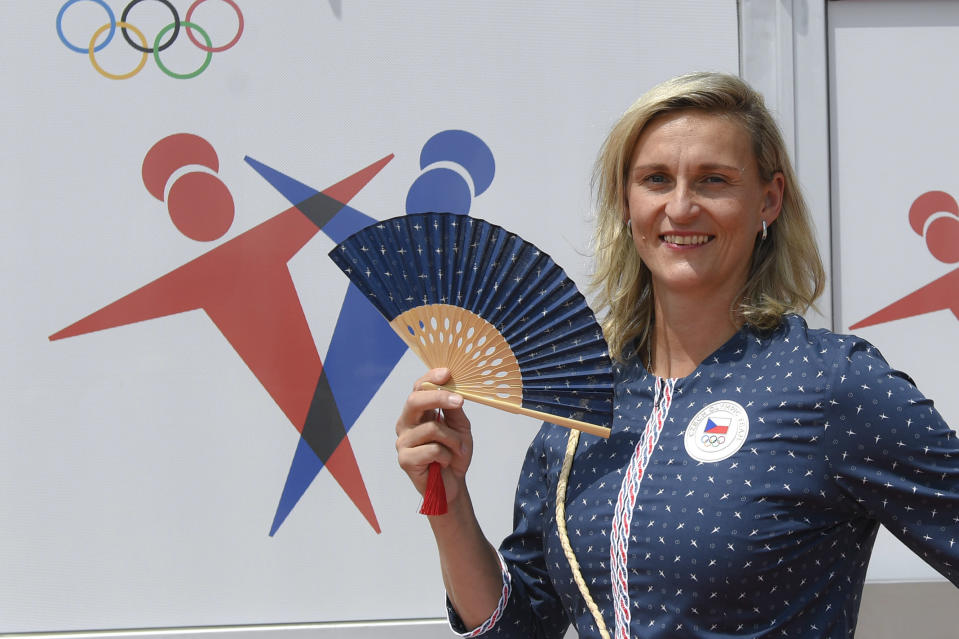 In this July 13, 2021 photograph Czech javelin thrower Barbora Sportakova poses for photographers wearing the new Czech Olympic uniform for The Tokyo Olympic Summer Games 2020 in Prague, Czech Republic. The Olympics in Tokyo open July 23, when the world's athletes will march behind their flag-bearers. And when they do, the peanut gallery on what they're wearing will be open, too. The year-long wait due to the pandemic has given enthusiasts extra time to ponder what they love or hate. There's the Czech Republic and its traditional indigo block-print design with matching fans _ already the butt of some jokes. (Michal Krumphanzl, CTK via AP)