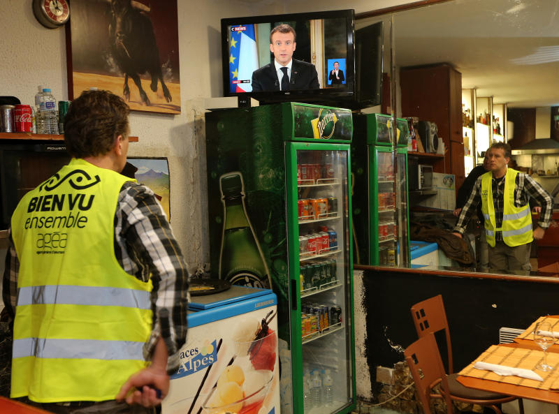 Yohann Piedagnel watches French President Emmanuel Macron during a televised address to the nation, in Hendaye, southwestern France, Monday, Dec. 10, 2018. In an unusual admission, French President Emmanuel Macron says he's partially responsible for anger fueling protests. (AP Photo/Bob Edme)