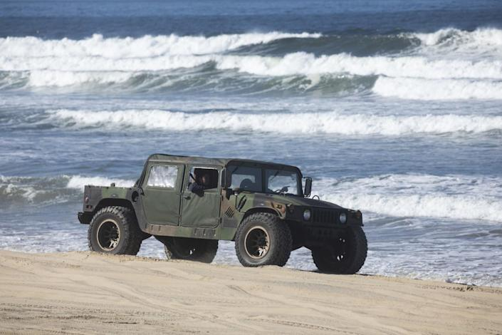 A military-style Humvee drives on on the beach near the water