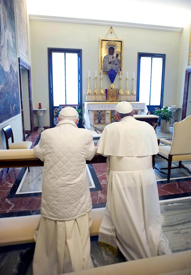 """In this photo provided by the Vatican paper L'Osservatore Romano, Pope Francis, right, and Pope emeritus Benedict XVI pray together in Castel Gandolfo Saturday, March 23, 2013. Pope Francis has traveled to Castel Gandolfo to have lunch with his predecessor Benedict XVI in a historic and potentially problematic melding of the papacies that has never before confronted the Catholic Church. The Vatican said the two popes embraced on the helipad. In the chapel where they prayed together, Benedict offered Francis the traditional kneeler used by the pope. Francis refused to take it alone, saying """"We're brothers,"""" and the two prayed together on the same one. (AP Photo/Osservatore Romano, HO)"""