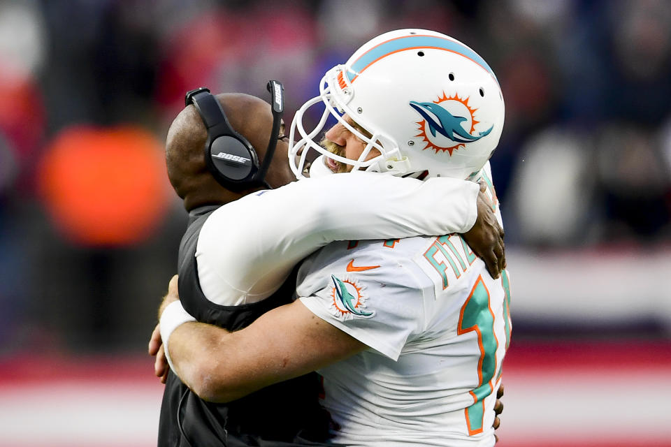 Ryan Fitzpatrick and Brian Flores celebrate a game-winning touchdown pass against the New England Patriots in the season finale last year. (Photo by Billie Weiss/Getty Images)