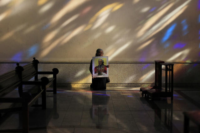 Adelina Hidalgo holds a photograph of Pope Benedict as she kneels inside the Metropolitan Cathedral in San Salvador February 11, 2013. Pope Benedict said on Monday he will resign on February 28 because he no longer has the strength to fulfil the duties of his office, becoming the first pontiff since the Middle Ages to take such a step. REUTERS/Ulises Rodriguez (EL SALVADOR - Tags: RELIGION POLITICS TPX IMAGES OF THE DAY) - RTR3DN6Y