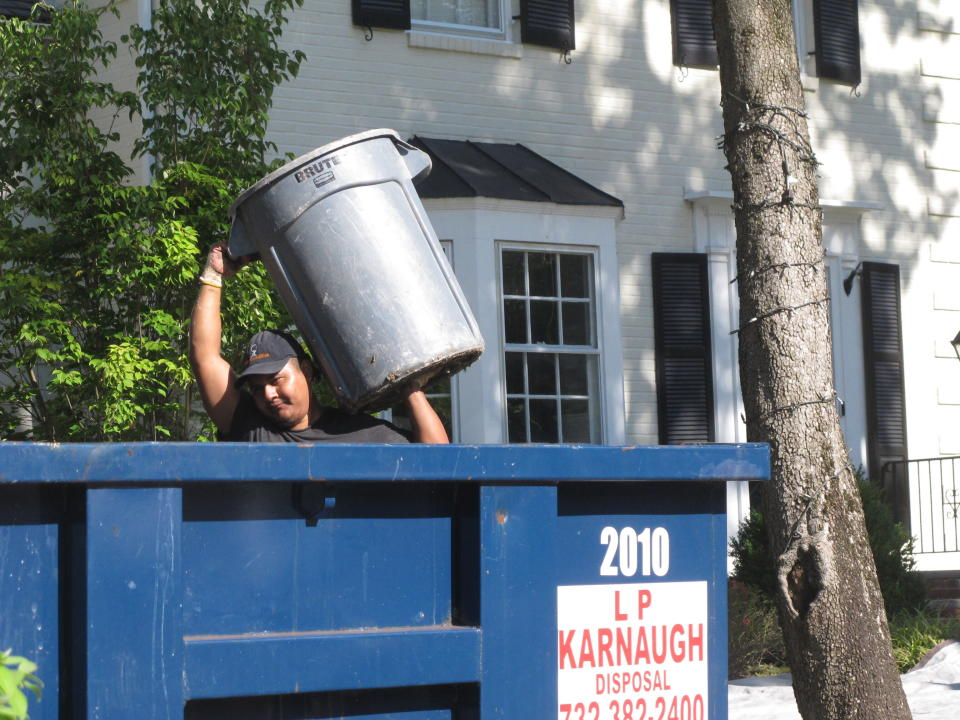 A man dumps debris into a receptacle in Cranford N.J. on Saturday Sept. 4, 2021, part of a massive cleanup effort under way to deal with damage caused by the remnants of Tropical Storm Ida. (AP Photo/Wayne Parry)