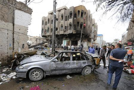 People look at the site of a car bomb attack in the neighbourhood of al-Qahera in northern Baghdad
