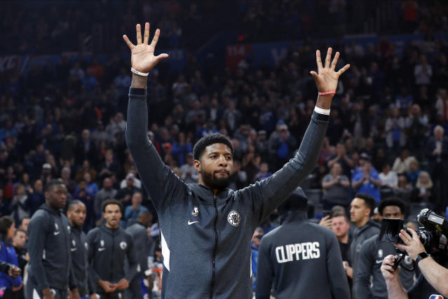 Los Angeles Clippers forward Paul George waves to Oklahoma City Thunder fans during introductions before an NBA basketball game Sunday, Dec. 22, 2019, in Oklahoma City. (AP Photo/Alonzo Adams)