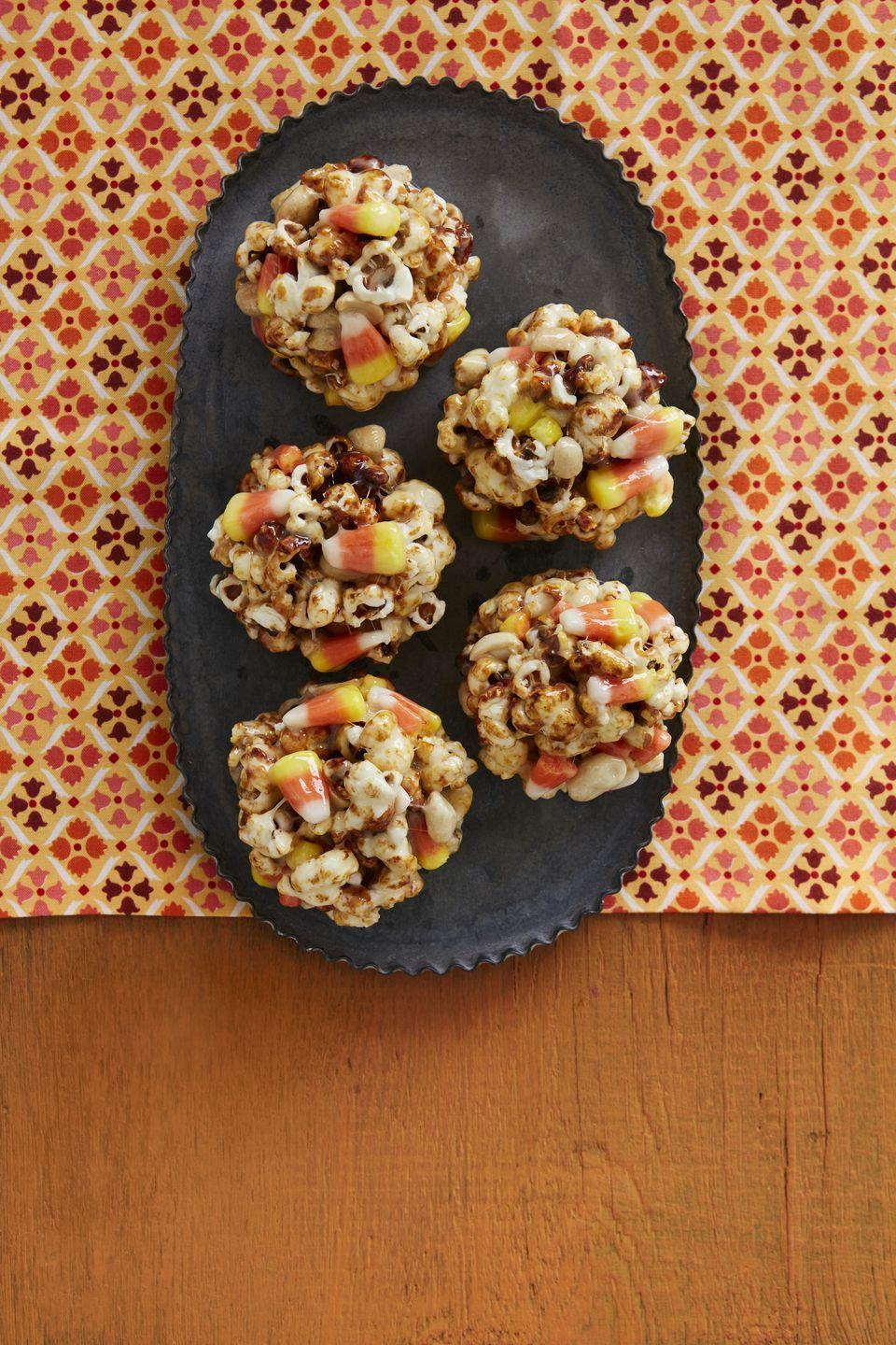 """<p>The combination of candy corn and popcorn would already be wonderful enough. But here, it's made even more marvelous with the addition of salted, roasted peanuts and mini marshmallows.</p><p><strong><a href=""""https://www.thepioneerwoman.com/food-cooking/recipes/a34029904/candy-corn-popcorn-balls-recipe/"""" rel=""""nofollow noopener"""" target=""""_blank"""" data-ylk=""""slk:Get the recipe."""" class=""""link rapid-noclick-resp"""">Get the recipe.</a></strong></p><p><a class=""""link rapid-noclick-resp"""" href=""""https://go.redirectingat.com?id=74968X1596630&url=https%3A%2F%2Fwww.walmart.com%2Fsearch%2F%3Fquery%3Dthe%2Bpioneer%2Bwoman%2Bserving%2Bplatters&sref=https%3A%2F%2Fwww.thepioneerwoman.com%2Ffood-cooking%2Fmeals-menus%2Fg32110899%2Fbest-halloween-desserts%2F"""" rel=""""nofollow noopener"""" target=""""_blank"""" data-ylk=""""slk:SHOP SERVING PLATTERS"""">SHOP SERVING PLATTERS</a></p>"""