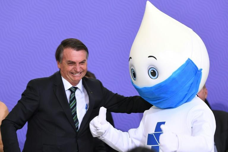 Brazilian President Jair Bolsobaro poses with Ze Gotinha, symbol of the national vaccination campaigns