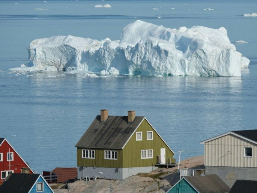 <p> An iceberg floats in Disko Bay behind houses during unseasonably warm weather on July 30, 2019 in Ilulissat, Greenland</p> (Getty Images)