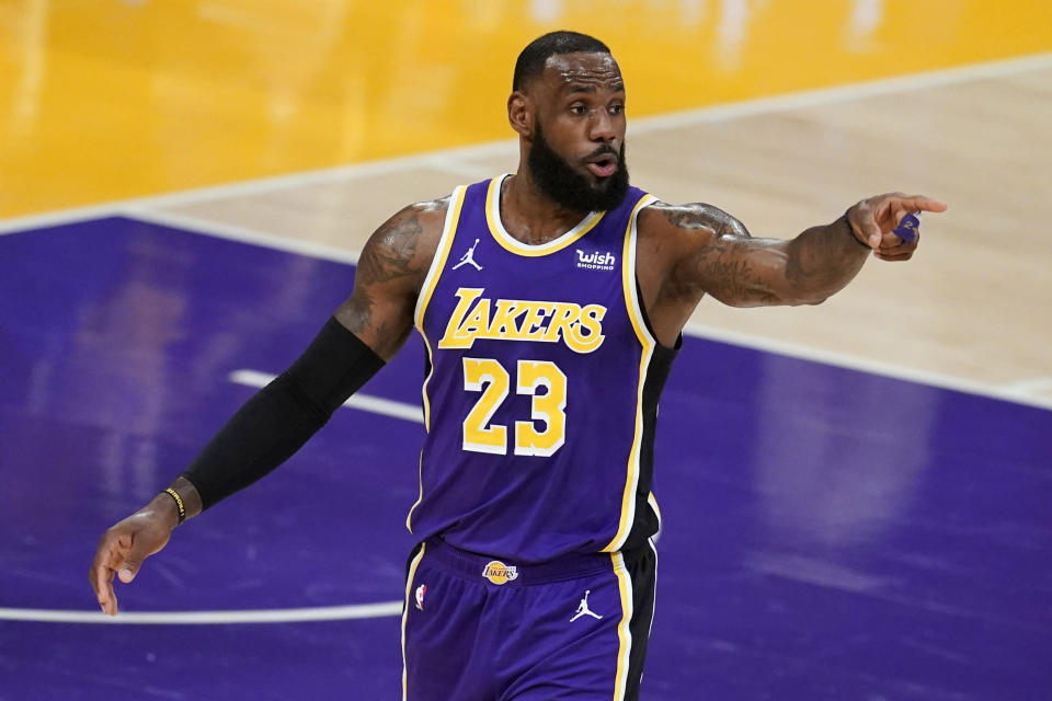 Los Angeles Lakers forward LeBron James signals to a teammate during the first half of an NBA basketball game against the Charlotte Hornets on Thursday, March 18, 2021, in Los Angeles. (AP Photo/Marcio Jose Sanchez)