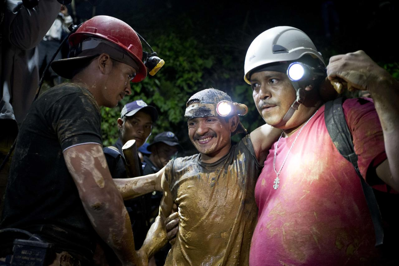 A rescued miner, center, is greeted by another miner while being helped by a rescue worker as he leaves the El Comal gold and silver mine in Bonanza, Nicaragua, Friday, Aug. 29, 2014. The first 11 of 24 freelance gold miners trapped by a collapse in a mine have been rescued and crews were working early Saturday to free more, officials said. (AP Photo/Esteban Felix)
