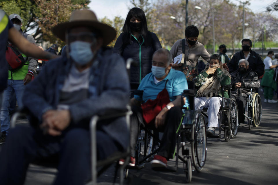 FILE - In this Feb. 24, 2021, file photo, elderly residents of the Iztacalco borough wait in line to receive doses of the Russian COVID-19 vaccine Sputnik V, during a mass vaccination campaign for Mexicans over age 60, at the Advanced School for Physical Education, in Mexico City. (AP Photo/Rebecca Blackwell, File)