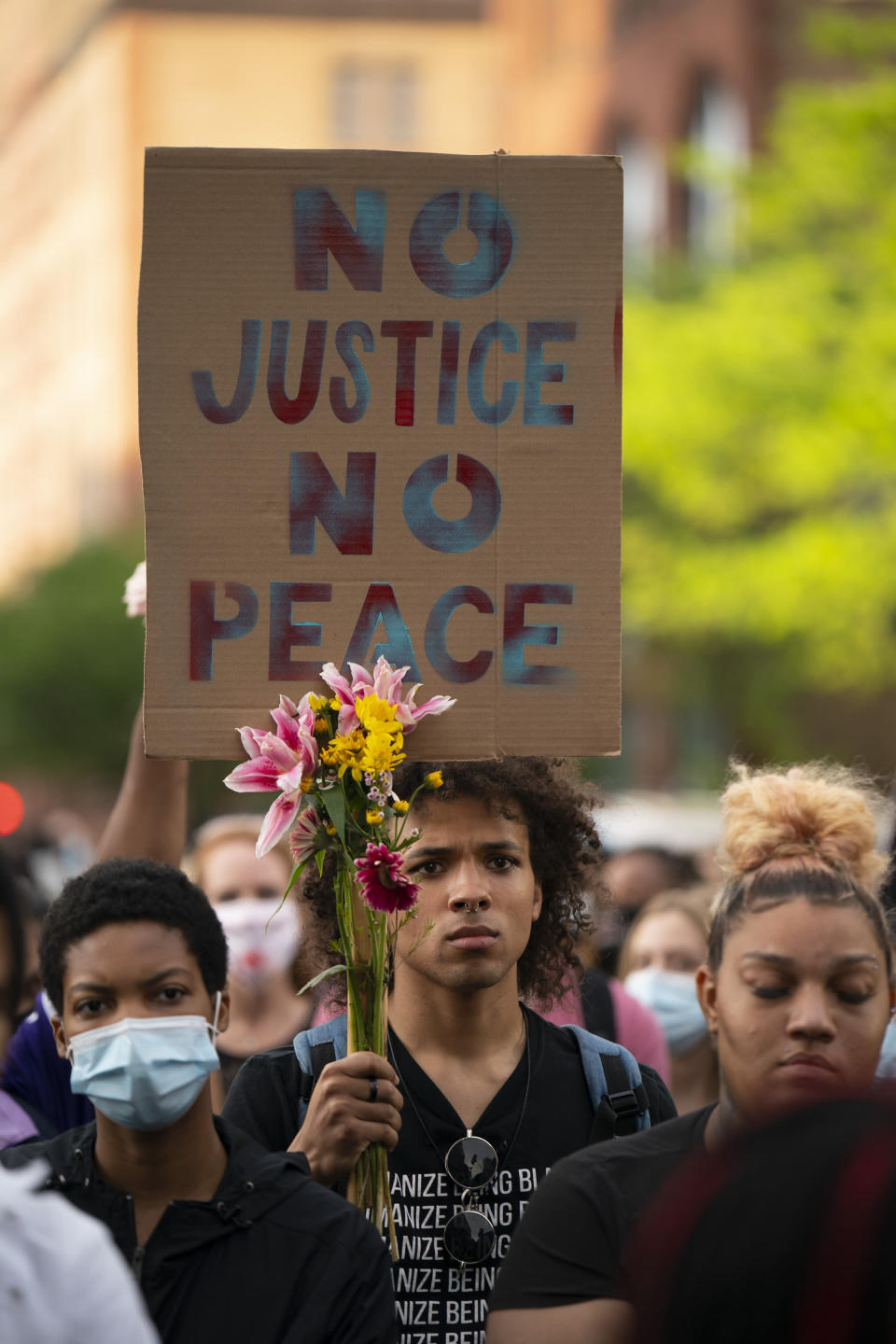People listen to a speaker during a rally and march in downtown Minneapolis, Sunday, May 23, 2021. Members of George Floyd's family, and others who lost loved ones to police encounters, joined activists and citizens in Minneapolis for a march that was one of several events planned nationwide to mark the one-year anniversary of Floyd's death. (Jeff Wheeler/Star Tribune via AP)