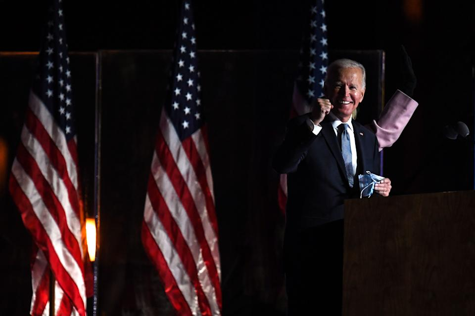 Joe Biden stands at a podium smiling in front of American flags, raising his right fist and holding his face mask with his left.