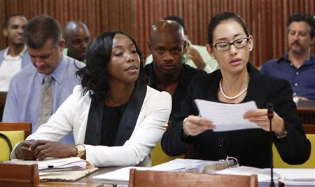 Jamaica's Olympic sprinter Simpson, who tested positive for doping at the Jamaican Championships in 2013, sits with her attorney Chai, as they wait for the beginning of the hearing before the country's anti-doping commission in Kingston