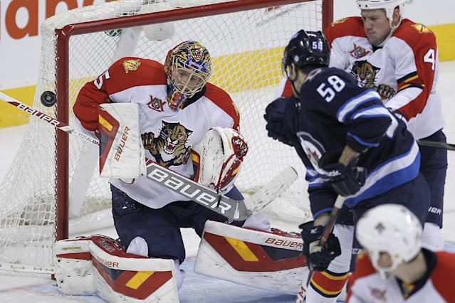 Winnipeg Jets' Eric O'Dell's (58) deflection is stopped by Florida Panthers goaltender Jacob Markstrom, left, as Panthers' Dylan Olsen (4) attempts to move O'Dell from in front of the net during the third period of an NHL hockey game in Winnipeg, Manitoba on Friday, Dec. 20, 2013. (AP Photo/The Canadian Press, John Woods)