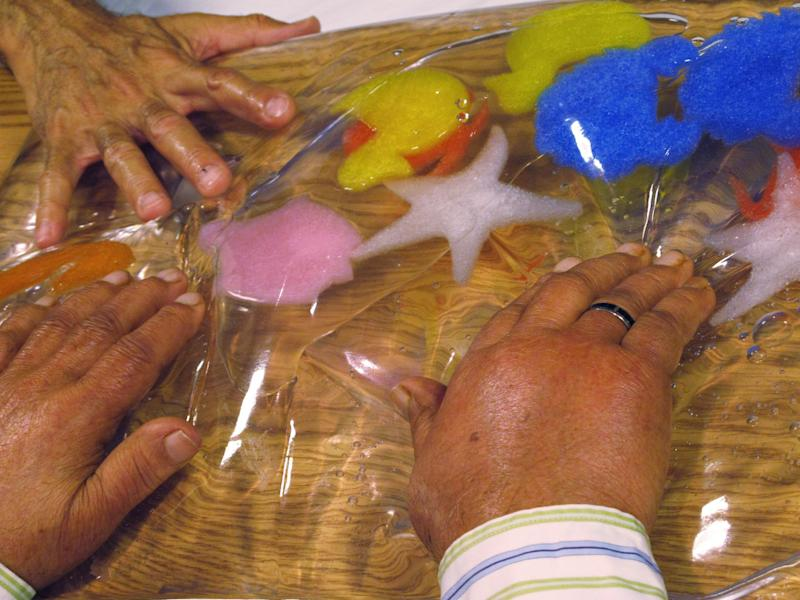 In this Sept. 20, 2012 photo, a staffer uses a water-filled toy to stimulate a dementia patient's sense of touch at the Hebrew Home at Riverdale in the Bronx borough of New York. The Hebrew Home has a program that provides care and activity overnight for dementia victims with sleep problems. (AP Photo/Jim Fitzgerald)