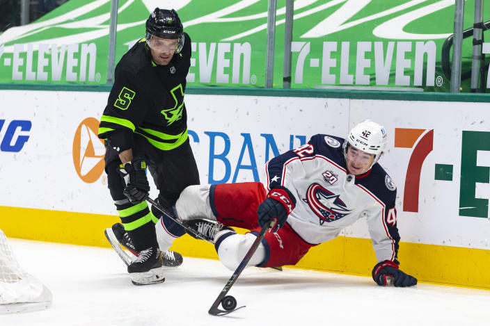 Columbus Blue Jackets center Alexandre Texier (42) dives for a loose puck in front of Dallas Stars defenseman Andrej Sekera (5) during the first period of an NHL hockey game Saturday, April 17, 2021, in Dallas. (AP Photo/Sam Hodde)