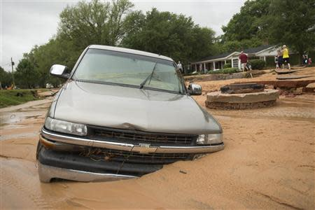 A vehicle is left partially submerged after flash flooding in the Cordova Park neighborhood in Pensacola, Florida, April 30, 2014. REUTERS/Michael Spooneybarger
