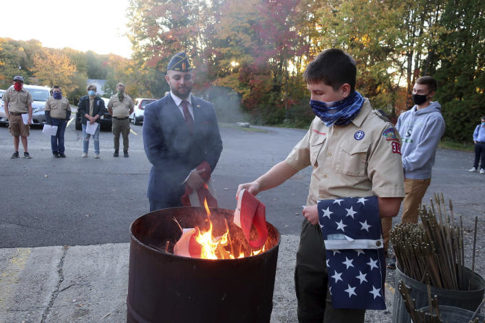FILE - In this Tuesday, Oct. 13, 2020 file photo, Jondavid Longo, Republican mayor of Slippery Rock, Pa., center, presides over a Boy Scouts flag retirement ceremony where worn out flags are cut up and burned in Slippery Rock. Longo says the 2020 election has changed politics in his town, surfacing resentments from voters on both sides. The lingering tensions now overshadow issues once considered local — such as funding the police and libraries. (AP Photo/Ted Shaffrey)