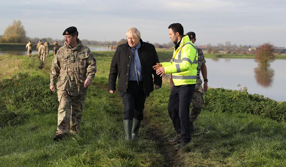 Britain's Prime Minister Boris Johnson (C) walks with Lt Col Tom Robinson (L) of the Light Dragoons and Oliver Harmar, Yorkshire Area Director of the Environment Agency as he visits Stainforth near Doncaster, northern England, on November 13, 2019, following flooding caused by days of heavy rain, and the River Don bursting its banks. (Photo by Danny Lawson / POOL / AFP) (Photo by DANNY LAWSON/POOL/AFP via Getty Images)