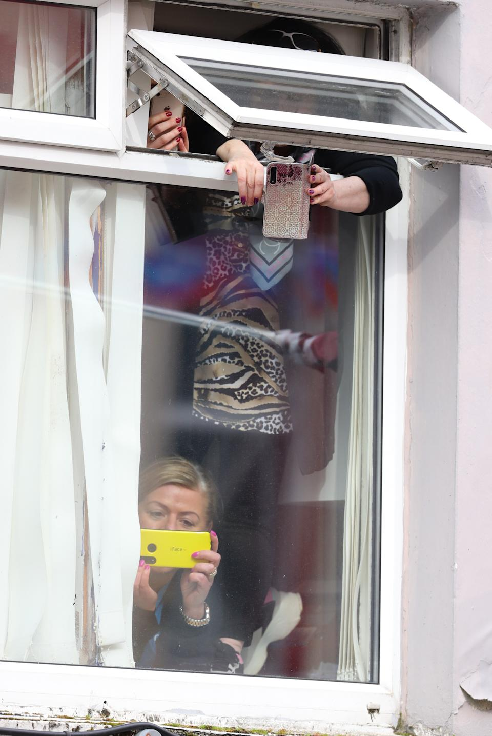People look out of a window as the Duchess of Cambridge meets local Galwegians after a visit to a traditional Irish pub in Galway city centre on the third day of her visit to the Republic of Ireland.