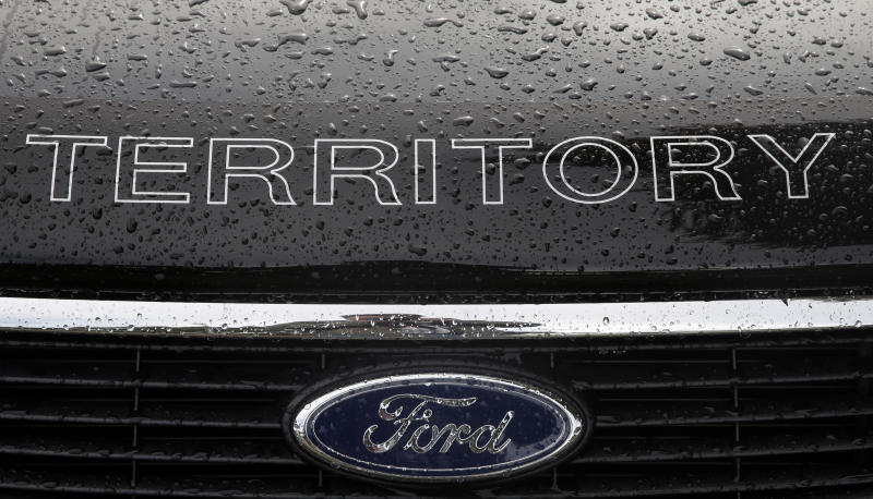 Rain falls on a car at a Ford dealership in Sydney on Thursday, May 23, 2013. Ford Motor Co. said it was closing its two Australian auto plants and ending production in the country in 2016, amid soaring manufacturing costs and plummeting sales. (AP Photo/Rick Rycroft)