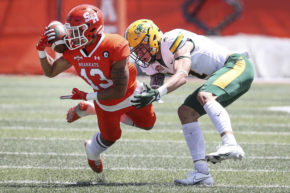 Sam Houston State defensive back Isaiah Downes (13) intercepts a pass intended for North Dakota State wide receiver Christian Watson (1) during the first quarter of a quarterfinal game in the NCAA college FCS football playoffs on Sunday, May 2, 2021, in Huntsville, Texas. (Brett Coomer/Houston Chronicle via AP)