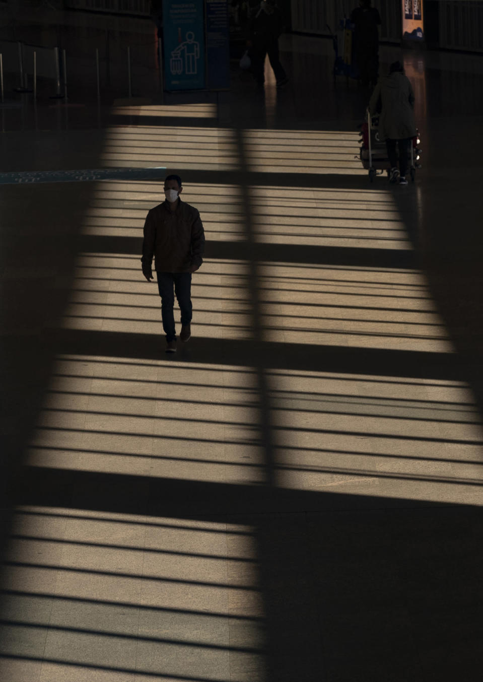 A man walks through an almost empty corridor inside the Sao Paulo International Airport in Guarulhos, Brazil, Wednesday, May 27, 2020. According to the airport administration, Brazil's busiest airport has had an average reduction of 85% in flights, due to the COVID-19 pandemic. (AP Photo/Andre Penner)