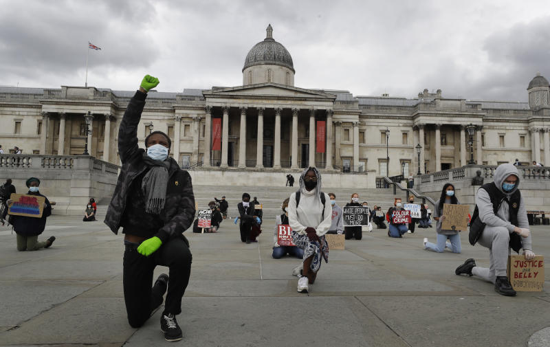 Demonstrators kneel in Trafalgar Square in London, Friday, June 5, 2020, to protest against the recent killing of George Floyd by police officers in Minneapolis, USA, that has led to protests in many countries and across the US. A US police officer has been charged with the death of George Floyd. (AP Photo/Kirsty Wigglesworth)
