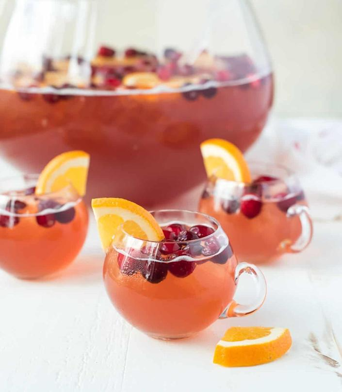 """<p>This punch gets a lovely fizz from two bottles of sparkling wine. The sweet cider and tart cranberry juice balance the drink out perfectly.</p><p><strong>Get the recipe at <a href=""""https://www.wellplated.com/christmas-punch/"""" rel=""""nofollow noopener"""" target=""""_blank"""" data-ylk=""""slk:Well Plated by Erin"""" class=""""link rapid-noclick-resp"""">Well Plated by Erin</a>.</strong> </p>"""