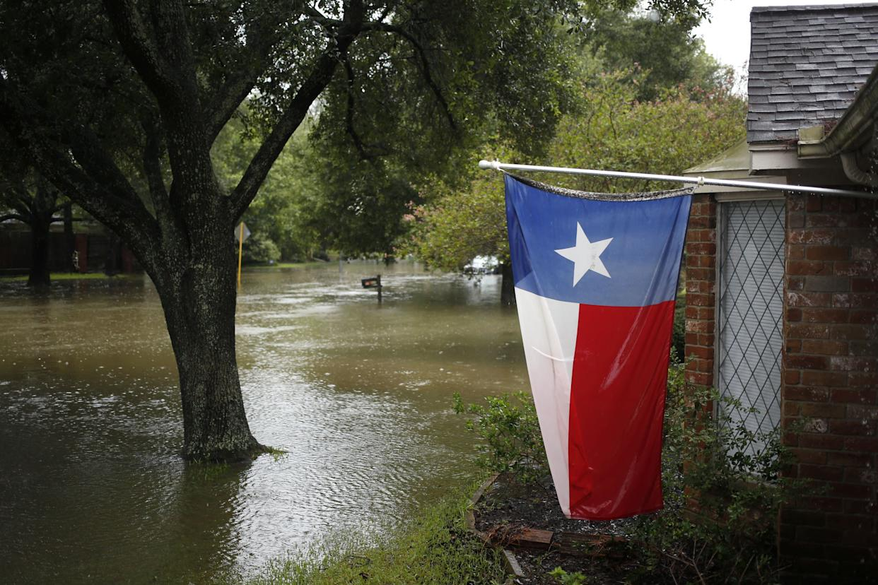 A Texas flag hangs from a home surrounded by floodwaters from Hurricane Harvey in The Woodlands.