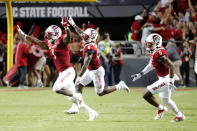 North Carolina State players run onto the field after they defeated Clemson in double overtime at an NCAA college football game in Raleigh, N.C., Saturday, Sept. 25, 2021. (AP Photo/Karl B DeBlaker)