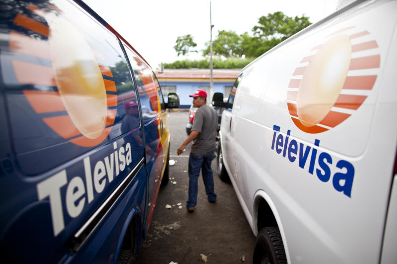 In this photo taken Wednesday, Aug. 29, 2012, a plain clothes Nicaraguan police officer stands between two vans bearing the logo of Mexican news channel Televisa, confiscated from a group of Mexican nationals posing as journalists, in Managua, Nicaragua.  Nicaraguan police say the group was detained while attempting to drive the vans to Costa Rica, transporting millions of dollars, to pay for a load of drugs that had been smuggled into the United States. The Aug. 20 seizure has pulled back the curtain on Nicaragua's role as a conduit between South American cocaine producers and the Mexican drug cartels that move their product into the United States. (AP Photo/Esteban Felix)