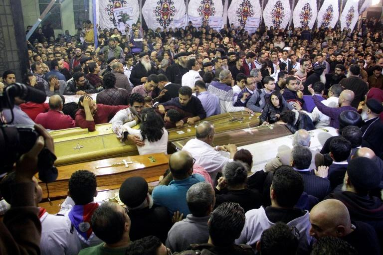 Egyptian Christians gather around and mourn by coffins during the late night funeral of the victims of a blast which killed worshippers attending Palm Sunday mass at the Mar Girgis Coptic Orthodox Church in the Nile Delta City of Tanta on April 9, 2017